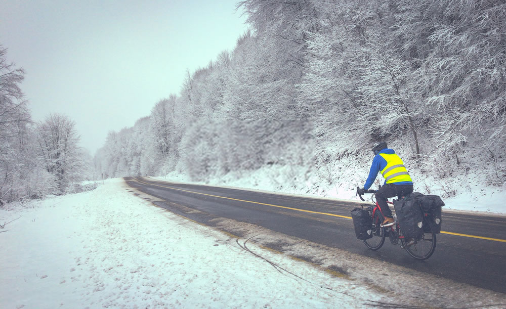 Male man in black and bue is cycling on fully loaded touring bicycle in winter conditions in nature covered in snow on wet asphalt with no cars